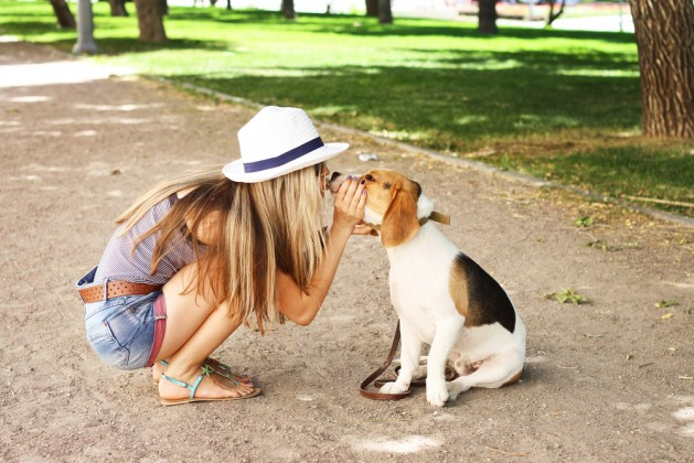 Cute girl kissing her beagle dog in nature outdoors. Lovely shot