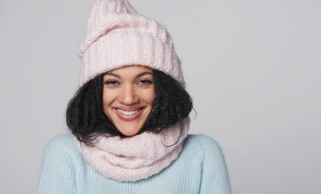 Laughing mixed race african american - caucasian girl wearing knitted sweater and hat with scarf, over gray background