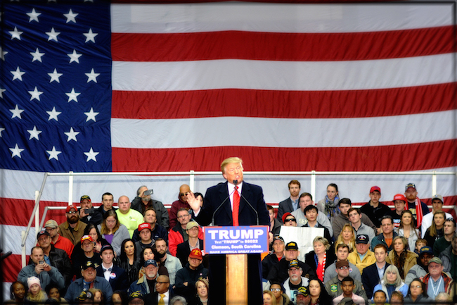 donald trump standing on stage speaking in front of an american flag