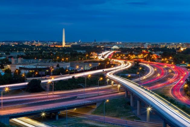 Washington D.C. cityscape at dusk with rush hour traffic trails on I-395 highway. Washington Monument, illuminated, dominates the skyline