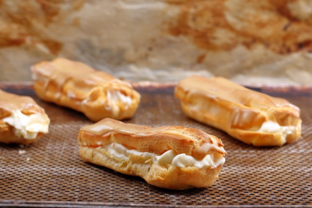 Sweet eclairs with cream. Catering set