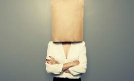 businesswoman hiding under empty paper bag over dark background