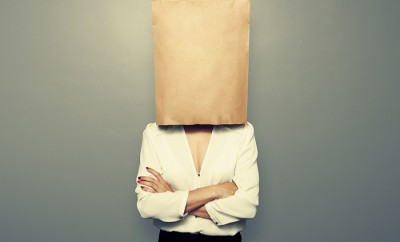 businesswoman hiding under empty paper bag over dark background