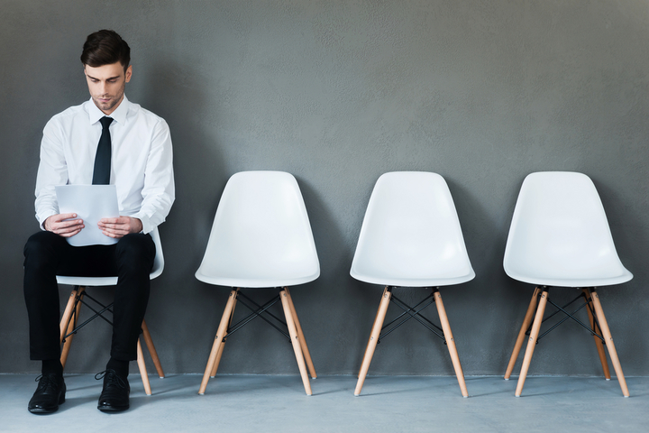Waiting for interview. Confident young businessman holding paper while sitting on chair against grey background