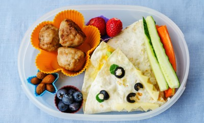school-lunch-box-for-kids-with-food-in-the-form-of-funny-faces-the-toning-selective-focus
