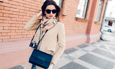 Beautiful and young girl in a coat and scarf and sunglasses walking around the city in the summer