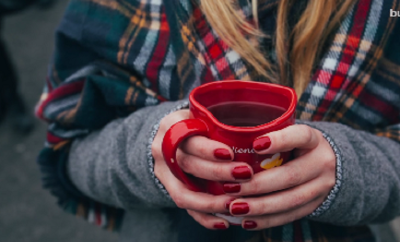 fall woman with red nails holding coffee mug in plaid scarf and coat