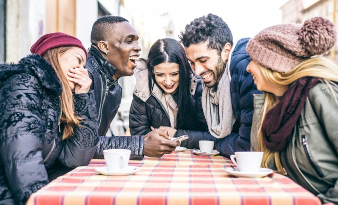multi-ethnic-group-of-friends-sitting-in-a-bar-and-drinking-coffee-and-watching-a-funny-video-on-a-cellular-phone-cheerful-students-meeting-in-a-coffee-house-for-a-break