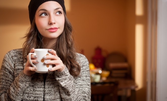 portrait of a gorgeous young brunette relaxing with cup of hot beverage