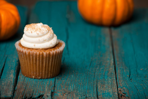 Pumpkin cupcake on blue background with mini pumpkin