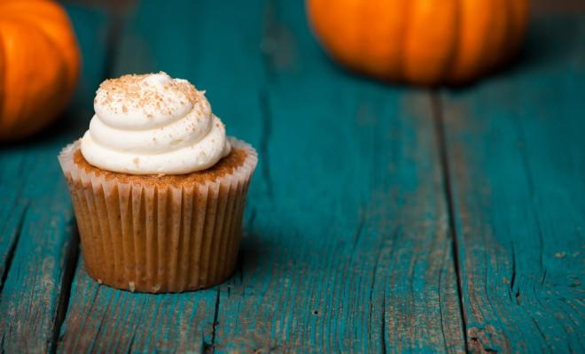 Pumpkin cupcake on blue background with mini pumpkin