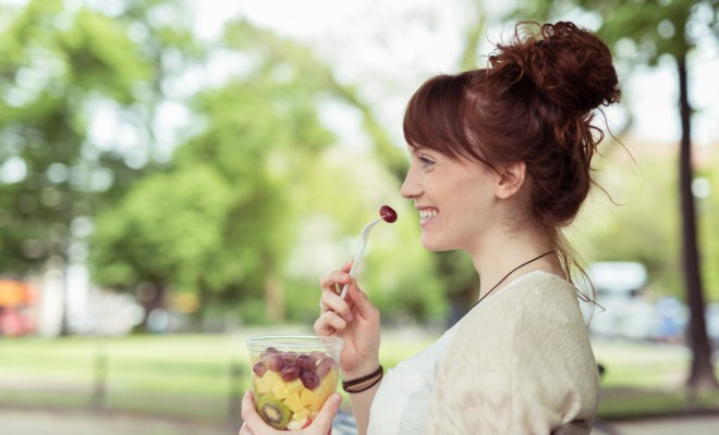 side view of a smiling pretty young woman at the park eating fresh fruit salad on a plastic container while looking into distance