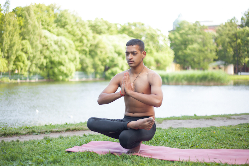 sporty-handsome-indian-young-man-working-out-on-mat-on-lake-in-park-sitting-in-squat-doing-half-lotus-toe-balance-padangustha-padma-utkatasana-hands-in-namaste-full-length