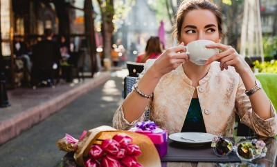 young stylish woman, fashion sunglasses, sitting in cafe, holding drinking cup cappuccino, enjoying, tulips, happy birthday party, city street, boho outfit, europe vacation, romantic dinner, sunny