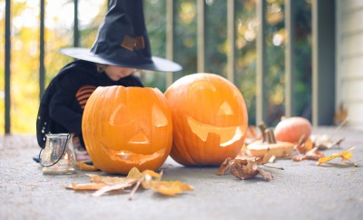 Little girl in a costume of a witch sitting near two pumpkins and a lantern