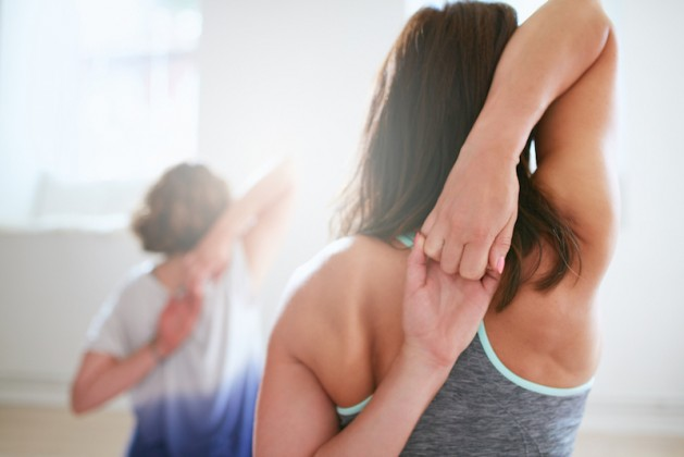 Rear view of fit woman doing gomukhasana in yoga class. Fitness female holding hands behind their back and stretching. Triceps and shoulders workout
