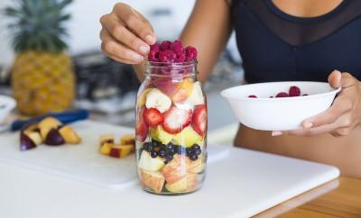 Sportive woman preparing her breakfast in a mason jar
