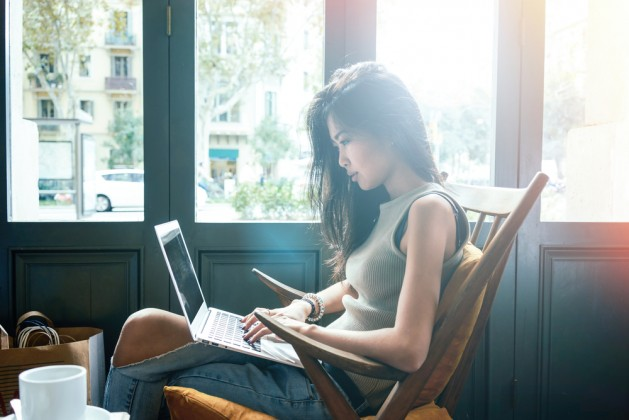 Beautiful young Asian girl working at a coffee shop with a laptop.female freelancer connecting to internet via computer.flare light
