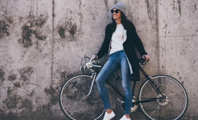 That was great ride! Beautiful young woman in sunglasses holding hands on her bicycle and looking away with smile while standing against concrete wall outdoors