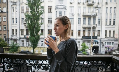 Beautiful young girl with a cup of morning coffee standing on the balcony in the rain. Thinking concept.