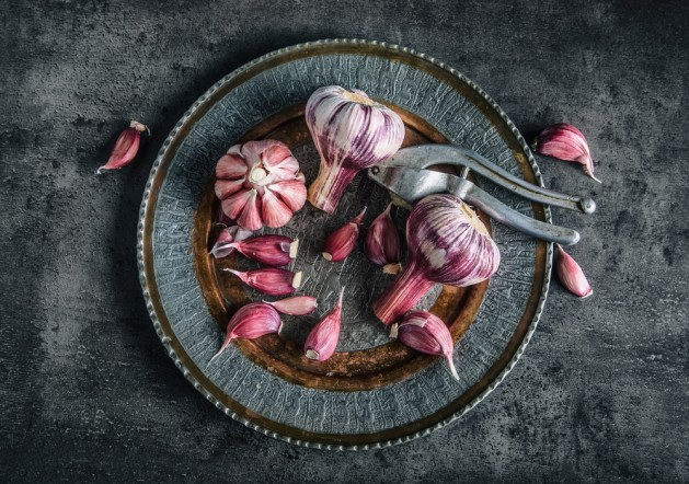 Garlic. Fresh garlic. Red garlic. Garlic press. Violet garlic.Garlic background. garlic bulbs. Slate board. Wooden board