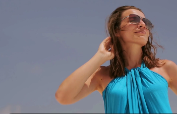 woman in blue with sunglasses outside happy