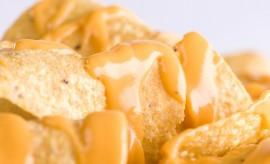 Close-up of yellow tortilla chips covered in nacho cheese on the Grey Background