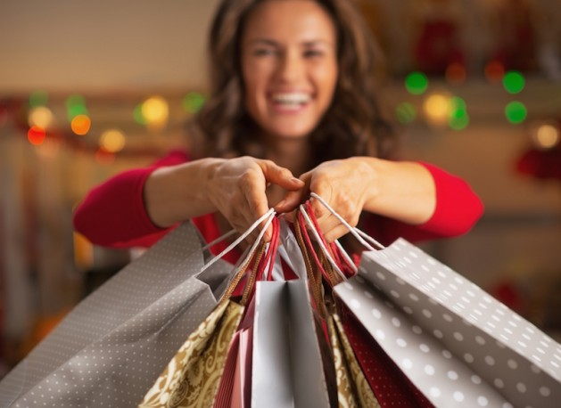 Closeup on christmas shopping bags in hand of smiling young woman