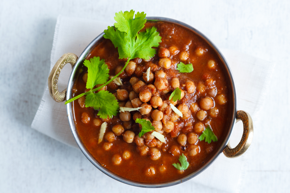 Chana Masala - Spicy Chickpea Curry , Indian Dish Chickpeas soaking in a bed of Onion Tomato gravy, garnished with Coriander leaves and Ginger Juliennes
