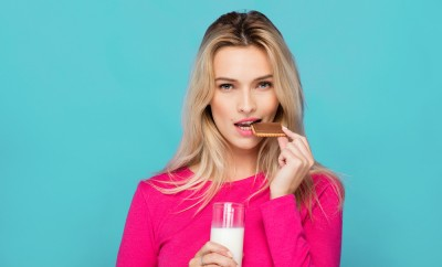 blonde young woman in pink blouse eating chocolate biscuit with milk on blue background