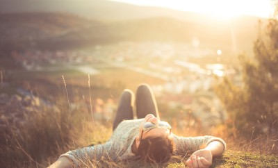 carefree-happy-woman-lying-on-green-grass-meadow-on-top-of-mountain-edge-cliff-enjoying-sun-on-her-face-enjoying-nature-sunset-freedom-enjoyment-relaxing-in-mountains-at-sunrise-sunshine-daydreaming