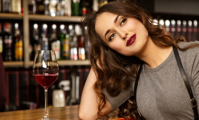 me-and-my-dreams-portrait-of-a-gorgeous-red-lipped-young-woman-looking-away-dreamily-smiling-while-having-a-glass-of-wine-at-the-bar-single-woman-millennial