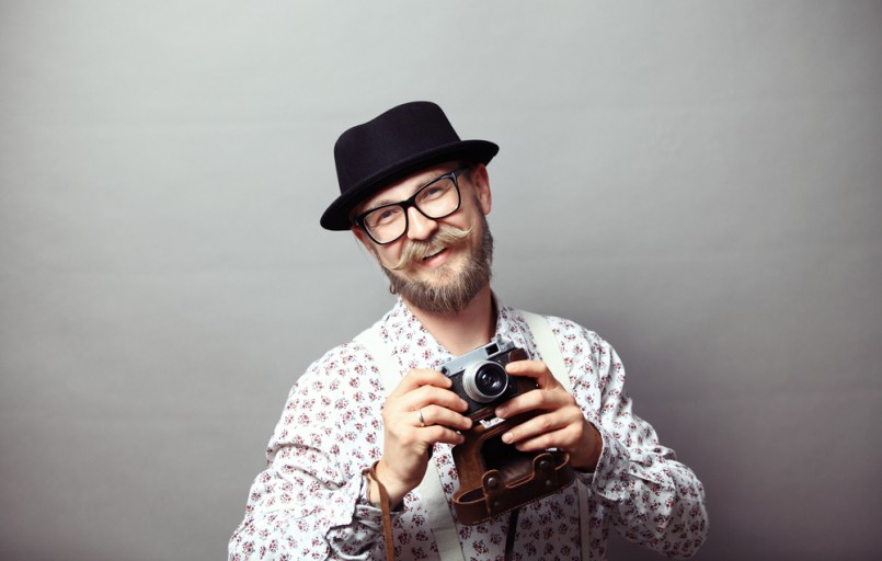 portrait-of-young-hipster-in-a-hat-holding-a-camera