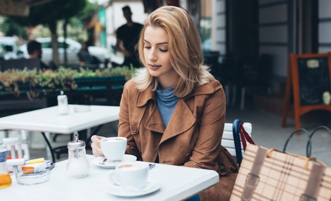 beautiful-blond-woman-sitting-alone-in-cafeteria-and-drinking-coffee