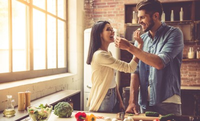 beautiful-young-couple-is-feeding-each-other-and-smiling-while-cooking-in-kitchen-at-home