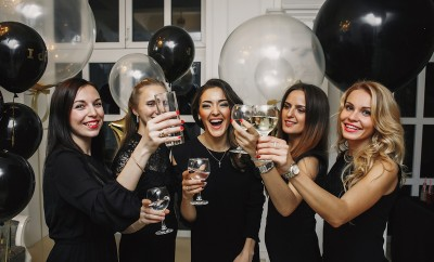 Cheers!Crazy party time of beautiful stylish women in elegant casual black outfit celebrating new year, birthday,having fun,dancing,drinking alcohol cocktails. Black and gold Balloons on Background women celebrating Galentine's Day
