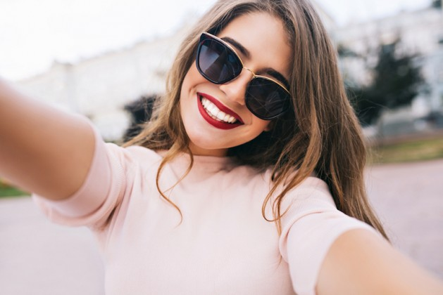 Closeup selfie-portrait student of attractive girl in sunglasses with long hairstyle and snow-white smile in city, ready for spring