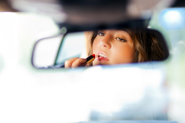 Cute blond woman applying lipstick in a car perfectionist applying lipstick, sad woman, stressed