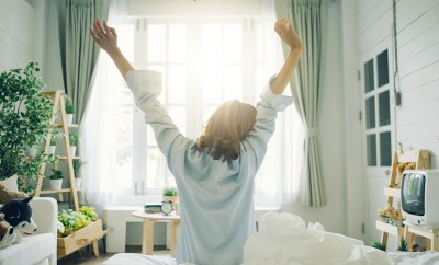 silhouette-of-cropped-shot-of-woman-stretching-in-bed-after-wake-upflare-light