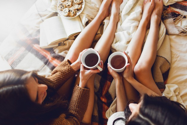 soft-photo-of-two-sisters-on-the-bed-with-old-books-and-cup-of-tea-in-hands-wearing-cozy-sweater-top-view-point-two-best-friends-enjoying-morning