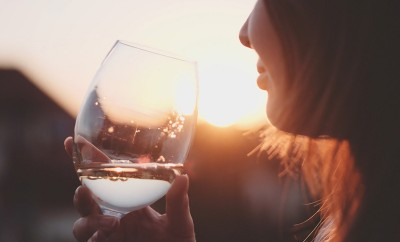 Woman Drinking Cooled White Wine from a glass at the Balcony during Sunset. Beautiful female enjoying cozy evening on terrace. Summertime relax at sunny patio. Lens Flare