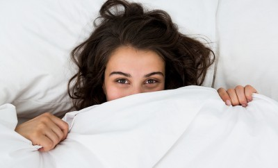 Woman hiding under blanket on bed at bedroom