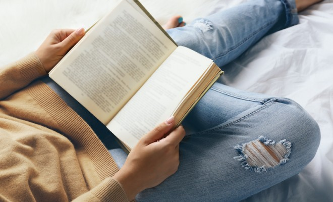Woman in blue jeans reading book on bed top view point reading to sharpen brain