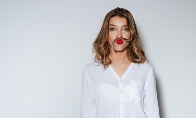 Young funny woman making mustache with a long strand of her hair in a humorous way over white background boost your mood