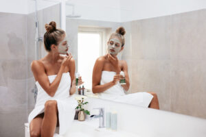 Young woman applying facial mud clay mask to her face in bathroom. Beautiful female wrapped in towel looking into mirror and doing facial beauty treatment.