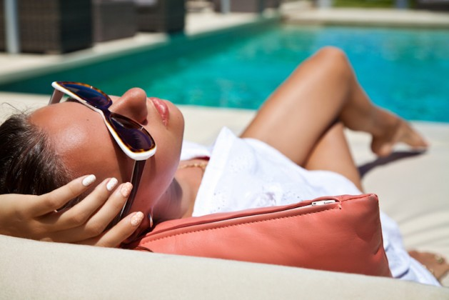 Portrait of sexy cheerful woman holding hand behind head, relaxing at the luxury poolside. Girl at travel spa resort pool. Summer luxury vacation. (focus on woman face), spring break destination