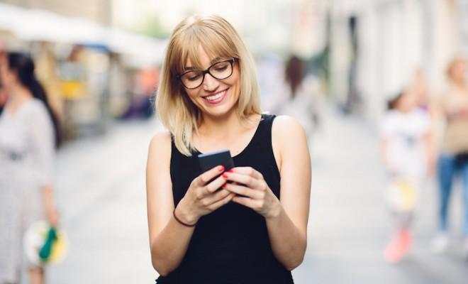 Smiling beautiful urban woman texting on the smart phone, phone, unplug