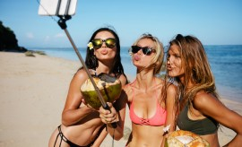 Three young women in swimsuit on the beach enjoying holidays and taking self portrait selfie stick. Group of female friends with coconuts taking selfie on the sea shore. Pout for a selfie on beach, how to eat for a healthy gut