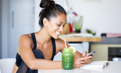 Woman drinking a homemade green detox juice, wearing sportive clothing, texting on her phone while sitting in her kitchen table high protein smoothies