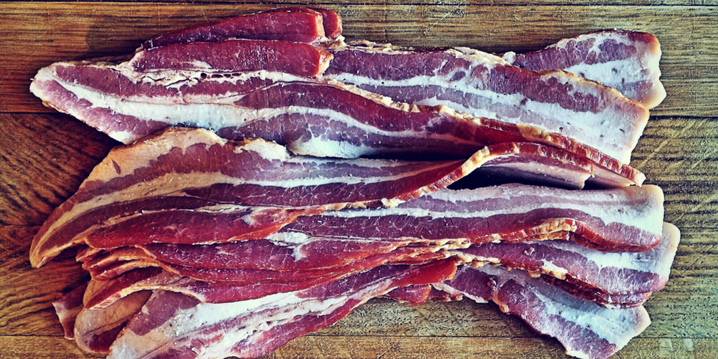 cured bacon on wood cutting board bacon strips
